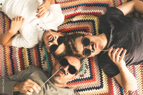 Photo Father and two sons enjoying together lying on a colorful blanket