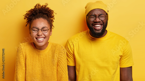 Isolated shot of overemotive joyful Afro teenage couple keep eyes closed, have toothy smiles, watch comedy together, wear yellow clothes, pose against studio wall Slika na platnu