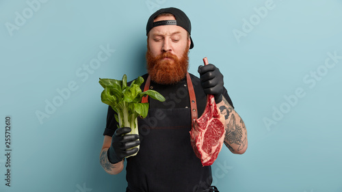 Fototapeta Indoor shot of male cook holds green bok choy in one hand and raw meat in other, going to bake pork, prepare fresh salad, cooks during working time, models over blue background. Nutrition concept obraz