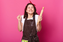 Baker Woman Holds Baking Rolling Pin, Wears Brown Apron, White T Shirt. Young Girl Bends Elbows And Shouts Yes With Closed Eyes, Female Maskes Cake First Time. Cook Isolated On Pink Background.