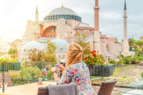 Fototapeta Girl drinks Turkish coffee enjoying the view of the Hagia Sophia Museum