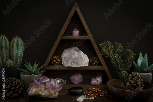Fototapeta  Triangular Crystal Shelf with Plants Foliage Gems and Jewellery on a Wooden Surf