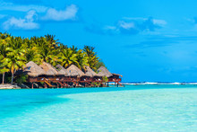 Stunning Tropical Aitutaki Island With Palm Trees, Water Bungalow, White Sand, Turquoise Ocean Water And Blue Sky At Cook Islands, South Pacific. Copy Space For Text.