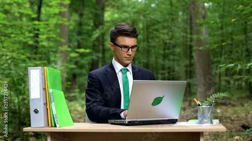 Fotografie, Obraz  Serious businessman working on laptop at office desk in forest, air conditioning