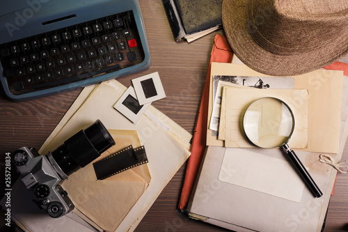 Stampa su Tela Investigator desk with confidential documents, camera, magnifying glass, vintage typewriter and hat