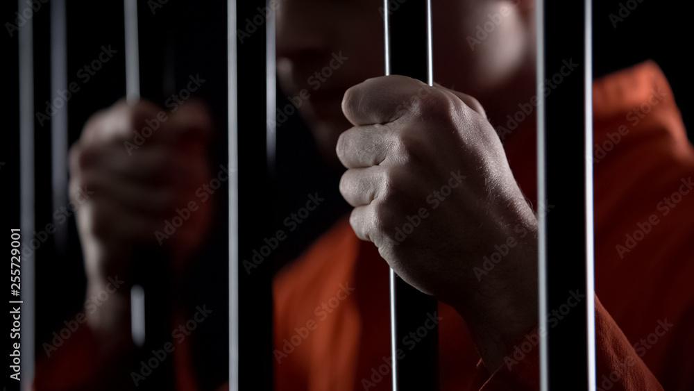 Fototapeta Desperate criminal holding jail bars feeling regret for committing crime closeup