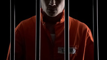 Criminal In Orange Uniform Behind Prison Bars, Serving Life Sentence For Murder