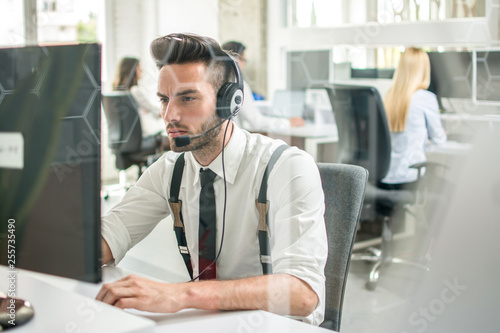 Fototapety, obrazy: Handsome young business man with headset talking with customer while working on computer in call center