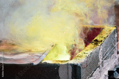 Fototapety, obrazy: Smoke Molten Gold being poured into Buddha statue in Thailand.
