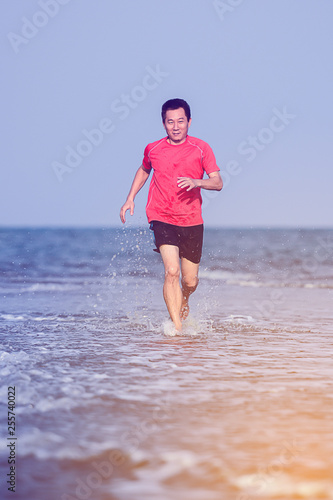 Fotografia  Motion blur Asian man running on the beach in evening, lifestyle concept