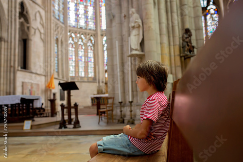 Canvas Print Little boy prays and puts a candle in Orthodox Church.