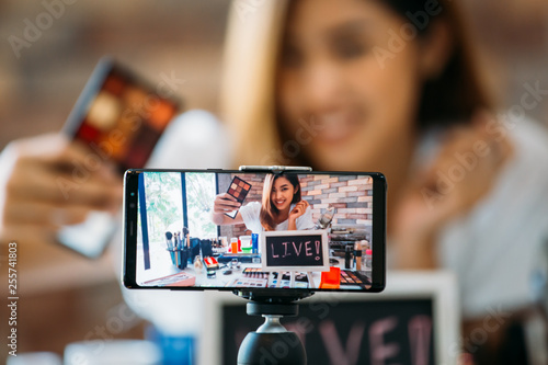 Foto  Happy young attractive Asian ethnic model filming vlog on mobile phone on tripod