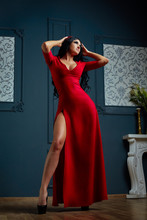 Sensual Young Woman In Red Dress. Studio Shot Of A Girl With Long Dark Hair.