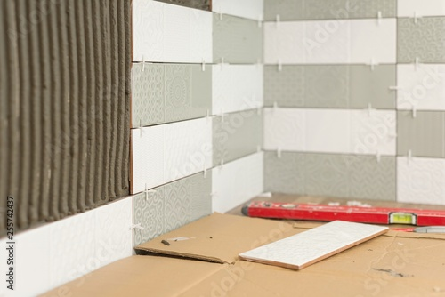 Fotografia  Process of laying ceramic tiles, construction and repair in the kitchen, tiles,