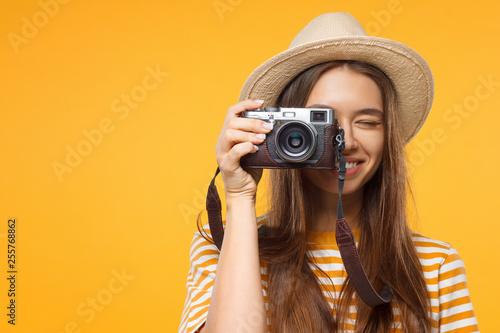 Fotografia  Close-up studio portrait of happy smiling young female tourist holding camera, i