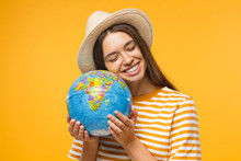 Planet Care, Save The Earth Concept. Cheerful Young Woman Hugging Globe, Isolated On Yellow Background