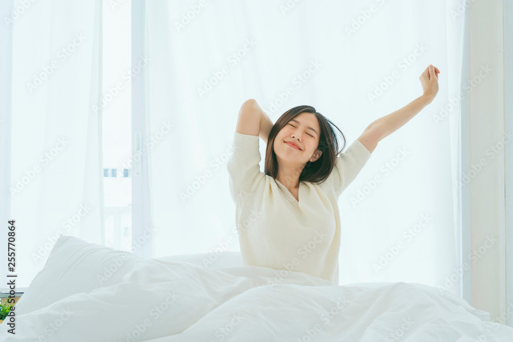 Fototapeta white dress asian beautiful woman stretching morning wake up bedroom with white curtain background lifestyle home concept