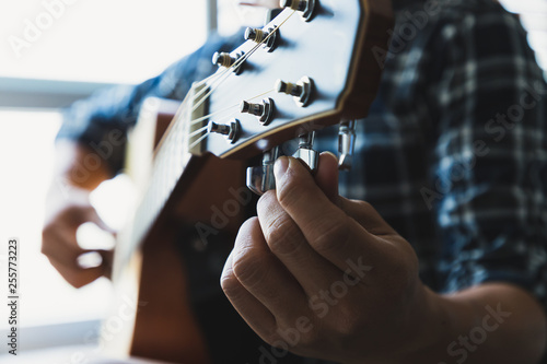 Fototapeta  Close up men wearing blue plaid shirts are setting the guitar