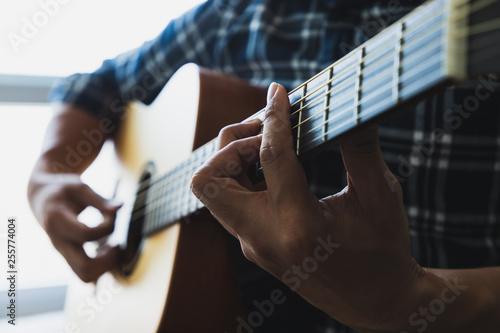 Obraz na plátne Close up men wearing blue plaid shirts playing guitar