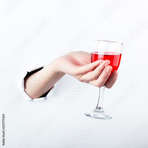 Fotografie, Obraz  Female hand out of the hole in the paperman, holding a glass of red wine