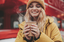 Happy Young Woman Holding Cup Of Coffee In Hands