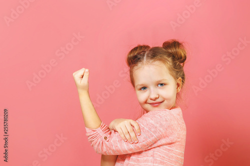 Fotografie, Obraz  Closeup portrait of cute kid with hair buns over pink background