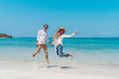 Young happy muslim couple white dress on seashore. Travel Vacation Retirement Lifestyle Concept. young couple jumping on the beach in vacation day. summer time.