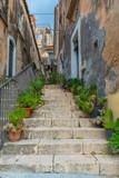 Fototapeta Uliczki - Narrow street with greenery in flower pots on the floor in Ragusa, Sicily, Italy