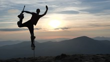 Man On The Stilts Jumps On One Leg On The Top Of Mountain.