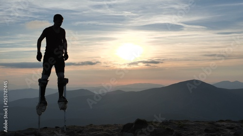Fotografie, Obraz Man on the stilts jumps on one leg on the top of mountain.