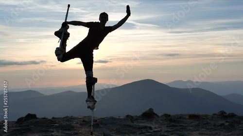 Man on the stilts jumps on one leg on the top of mountain. Fototapet