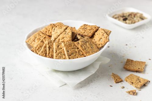 Fényképezés Thin crispy salted multigrain crackers with seeds on grey concrete background