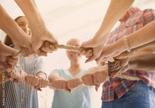 People holding rope together on light background, closeup of hands Tablou Canvas