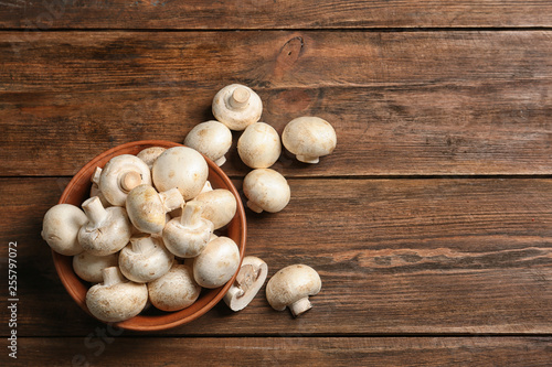 Bowl of fresh champignon mushrooms on wooden background, top view with space for Canvas Print