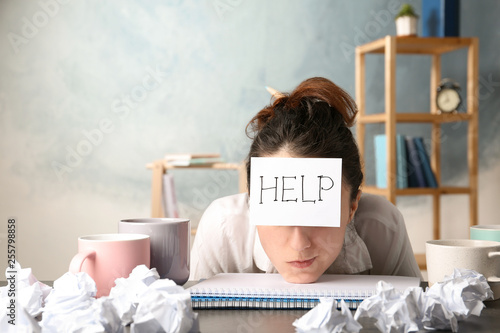 Fotomural Young woman with note HELP on forehead at workplace