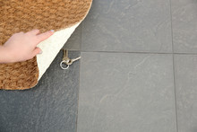 Young Woman Revealing Hidden Key Under Door Mat, Space For Text