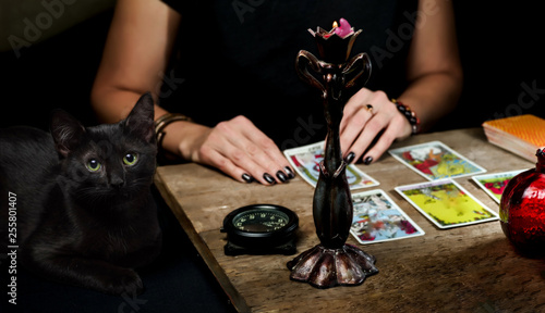 The fortune teller lays out on a wooden table the tarot cards by the light of a candle Canvas Print