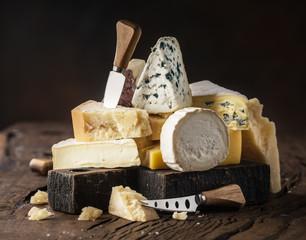 Asortyment różnych rodzajów serów na drewnianym tle. Serowy tło.