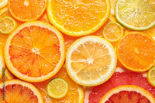 Poster Fruit Slices of fresh citrus fruits as background, top view
