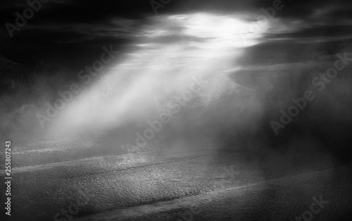 Foto op Canvas Onweer Background scene of empty street. Night view of the river, the night sky with clouds, a reflection of light on the asphalt. Smoke fog