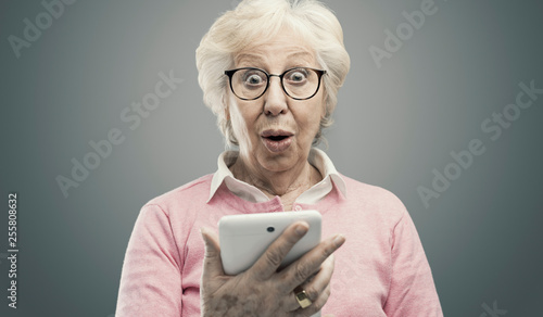 Foto Happy surprised senior lady using a tablet