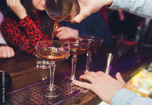 Male bartender is making cocktail pouring alcohol from shaker to glass at bar background Canvas Print