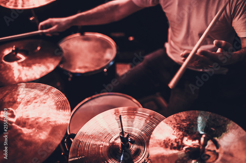 Fotografía music, people, musical instruments and entertainment concept - male musician or drummer playing drum kit at studio over holidays lights background