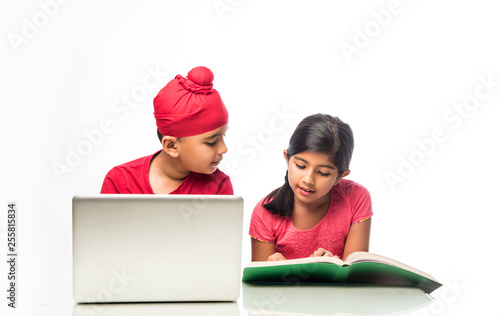 Fototapeta Indian sikh/Punjabi  boy and girl studying with books and laptop computer at stu