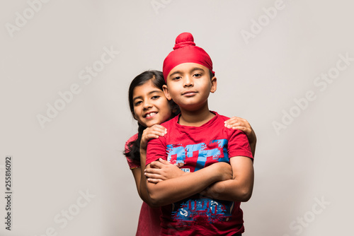 Fotografie, Tablou  cute little sikh/punjabi boy and girl standing isolated over white background, f