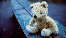 Concept: Loneliness, Pain And Depression. Dirty Teddy Bear Lying Down On An Old Broken Wooden Bench