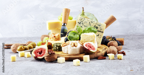 Fototapeta Cheese plate served with figs, various cheese on a platter on wood obraz