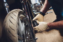 Man Fixing Bike. Confident Young Man Repairing Motorcycle Near His Garage. Caliper, Brake Pad Replacement