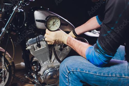Man fixing bike. Confident young man repairing motorcycle near his garage. barometer