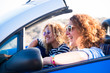 Couple of curly cheerful woman smiling and having fun together enjoying the travel vacation driving the car - people on the move in convertible vehicle in sunny day of summer